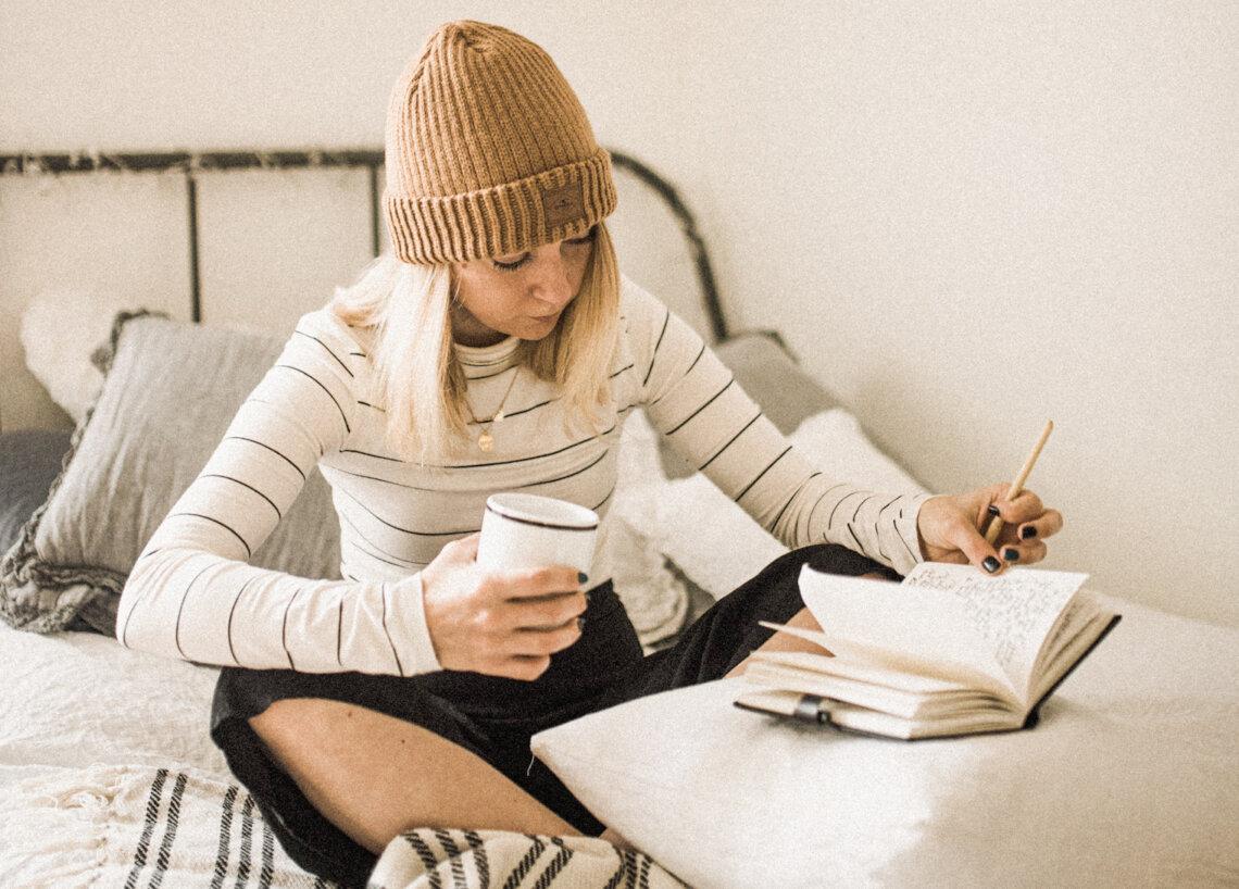 en ny rutin, kvinna skriver i ett block i en säng