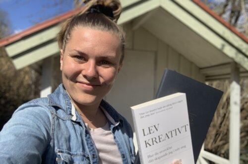 """Lev kreativt - Glad kvinna står med boken """"lev kreativt"""" i handen"""