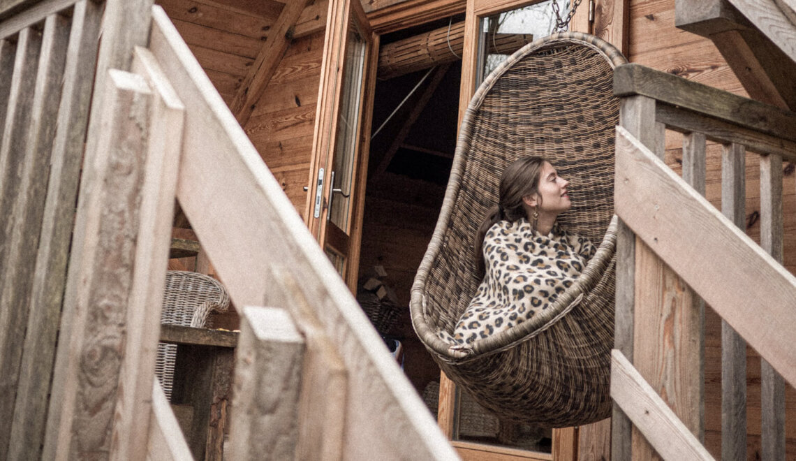 distansarbete, kvinna sitter med en leopardfärgad filt i en stor gunga.