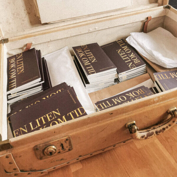 En liten bok om tid, flera exemplar placerade i gammal koffert