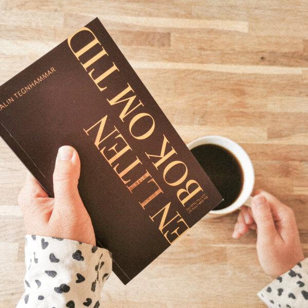 En liten bok om tid läses samtidigt som en kvinna håller i en kaffekopp
