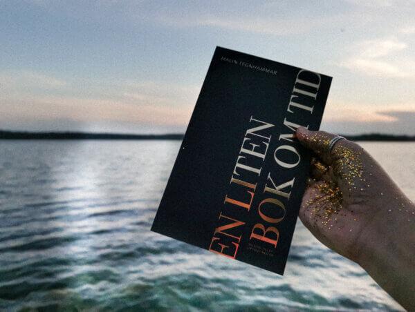 En liten bok om tid hålls av kvinna med glitter på handen