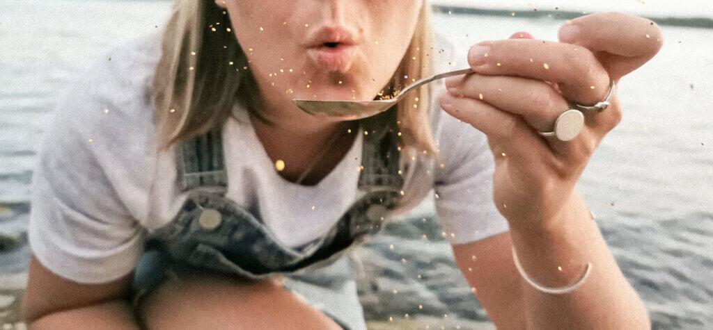 One spoon happiness, kvinna blåser glitter från en sked