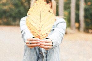 samla på lyckliga ögonblick_kvinnar håller ett stort gult löv framför kroppen