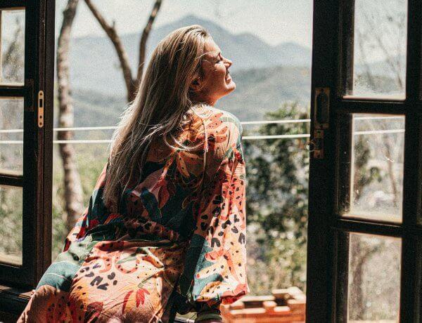 Uppnå dina mål - kvinna lutar sig ut genom öppet fönster